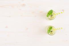 Struttura decorativa del frullato verde di recente mescolato del kiwi in barattoli di vetro con paglia, foglia della menta, vista Fotografia Stock