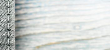 Struttura del denim su fondo di legno blu, confine fotografia stock
