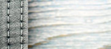 Struttura del denim su fondo di legno blu, confine immagine stock libera da diritti