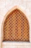 struttura del muro di mattoni e dell'uomo anziano marrone di legno della finestra triangolare islamica islamica araba scolpita an fotografia stock libera da diritti