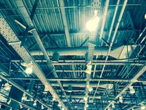 Struttura del soffitto del metallo del ferro con i tubi e le lampade nei cappucci del deposito del centro commerciale I cenni sto fotografia stock
