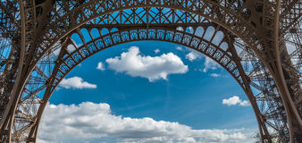 Struttura dell'arco del primo piano della torre Eiffel sopra il cielo nuvoloso blu a Parigi Francia Immagine Stock