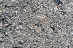 Struttura dell'asfalto della strada con molte crepe, le crepe, le ammaccature ed il primo piano delle buche immagine stock libera da diritti