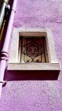 Struttura della finestra in Burano sulla parete porpora di colore immagini stock