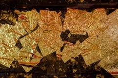 Struttura della foglia di oro, fondo dell'oro, immagine della sfuocatura dall'immagine di Buddha indietro, fondo della foglia di  fotografie stock