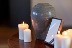 Struttura della foto, urna di cremazione e candele sulla tavola Immagini Stock