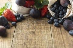 Struttura della frutta con le fragole, mirtilli, fichi su fondo strutturato rustico Fondo della frutta per la prima colazione con fotografia stock