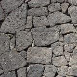 Struttura della parete nera della roccia vulcanica Immagine Stock