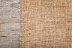 Struttura della tela da imballaggio sulla tavola di legno immagini stock