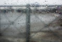 Struttura delle gocce del bokeh su vetro davanti al paesaggio urbano del parco immagini stock