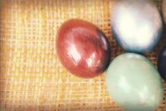 Struttura di carta d'annata, uova di Pasqua variopinte sullo shee di bambù del tessuto Immagini Stock