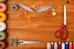 Struttura di Copyspace con gli strumenti e gli accessori di cucito su fondo di legno Immagini Stock Libere da Diritti
