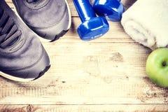 Struttura di forma fisica con le teste di legno, le scarpe da tennis e la mela verde Sano fotografia stock
