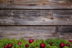 Struttura di legno di natale con muschio verde e palle rosse per una struttura Immagini Stock