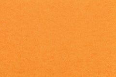 Struttura di vecchio fondo di carta arancio luminoso, primo piano Struttura del cartone denso della carota immagine stock