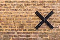 Struttura di vecchio muro di mattoni con un incrocio nero del metallo su  Fotografia Stock Libera da Diritti
