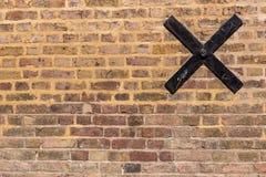 Struttura di vecchio muro di mattoni con un incrocio nero del metallo su  Immagini Stock Libere da Diritti