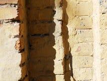 Struttura di vecchio muro di mattoni ocraceo con le ombre di illuminazione solare immagini stock libere da diritti