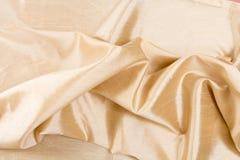 Struttura/fondo ondulati dorati del tessuto Fotografie Stock