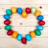 Struttura in forma di cuore delle uova di Pasqua colorate sopra la superficie di legno leggera come composizione festiva nel fond Fotografia Stock Libera da Diritti