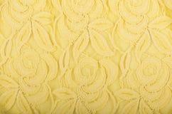 Struttura gialla del pizzo con il modello floreale su fondo bianco Immagine Stock