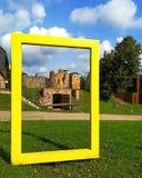 Struttura gialla Oggetto all'aperto davanti alle rovine storiche del castello, Estonia di arte fotografia stock libera da diritti