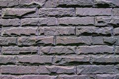 Struttura grigia dei mura di mattoni scuri per fondo Vecchia, superficie graffiata e irregolare immagini stock