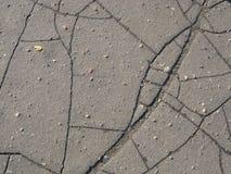 Struttura grigia incrinata dell'asfalto con le piccole pietre fotografie stock libere da diritti