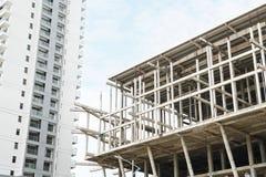 Struttura incompleta di architettura della costruzione del cantiere accanto all'appartamento completo del condominio di rivestime Fotografia Stock Libera da Diritti