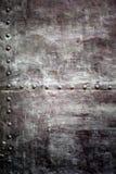 Struttura nera dell'armatura o di piastra metallica con i ribattini Fotografie Stock