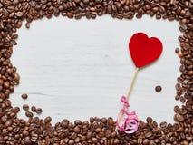 Struttura quadrata dei chicchi di caffè con cuore rosso su una tavola di legno, giorno del ` s del biglietto di S. Valentino Fotografia Stock Libera da Diritti