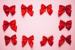 Struttura rossa degli archi del raso di Natale, insieme dei nastri su fondo rosa immagini stock libere da diritti