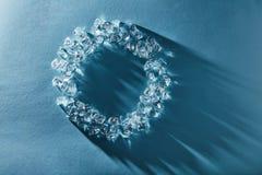 Struttura rotonda creativa dei cubetti di ghiaccio su un fondo blu Disposizione piana immagine stock libera da diritti
