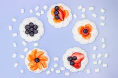 Struttura rotonda di meringa con i mirtilli, le fragole, la caramella gommosa e molle ed i mandarini su un fondo della lavanda Vi immagine stock