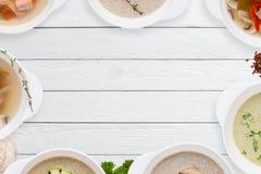 Struttura saporita differente delle minestre sulla disposizione di legno bianca del piano Fotografia Stock