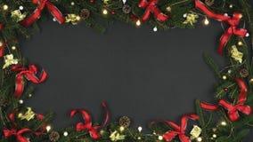 Struttura sopraelevata di ciclaggio della decorazione su fondo grigio scuro con le pigne, rami, nastri rossi dell'oro, luci inter stock footage