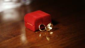 Struttura statica Due anelli di oro turbinano e filano su una tavola di legno vicino alle nozze rosse di caso stock footage