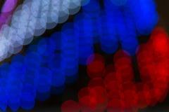 Struttura vaga astratta del bokeh da vari cerchi leggeri bianchi, blu, rosso dai colori della bandiera russa fotografie stock libere da diritti