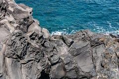 Struttura vulcanica di formazioni rocciose con il mare blu sull'immagine di sfondo immagine stock libera da diritti