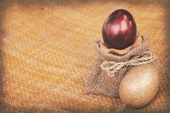 Strutture di carta d'annata, rosso ed uova di Pasqua dell'oro su tessuto di bambù Fotografie Stock