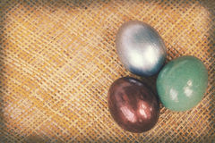 Strutture di carta d'annata, uova di Pasqua variopinte su tessuto di bambù Fotografia Stock