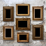 Strutture di legno dorate per le immagini sulla parete di pietra Immagine Stock