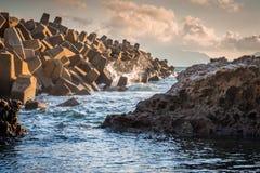 Strutture di tetrapodi sulla spiaggia durante il tramonto o il crepuscolo come protezione per le grandi onde a Wakamatsu, Fukuoka fotografia stock