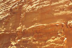 Strutture gialle del fondo in una parete di pietra naturale Fotografie Stock