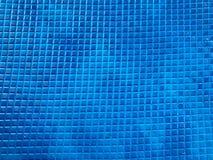 Strutturi la stuoia blu antisdrucciolevole di gomma con un modello di piccole mattonelle quadrate I cenni storici fotografia stock