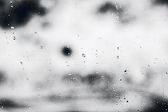 Strutturi le gocce di pioggia sul vetro di finestra per pioggia, i colori in bianco e nero, la foto, fondo insolito fotografie stock libere da diritti