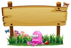 Struty różowy potwór pod pustym signboard Zdjęcia Royalty Free