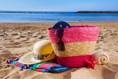 Strwa bag with sunbathing accessories on sandy Royalty Free Stock Photography