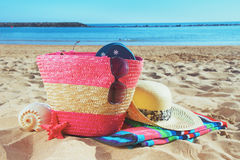 Strwa bag with sunbathing accessories on sandy Royalty Free Stock Photos