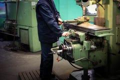 Stryker manliga arbeten för en arbetare på en större metall låssmeddrejbänken, utrustning för reparationer, metallarbete i ett se arkivfoton
